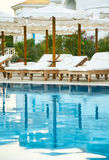 Klubsessel durch das Pool bei Sonnenuntergang setzen Zeit vertcal fest Lizenzfreies Stockfoto