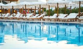 Klubsessel nahe dem Pool bei Sonnenuntergang setzen Zeit horizontales fest Lizenzfreie Stockbilder