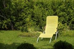 Klubsessel und Strohhut auf sonnigem Rasen stockfoto