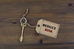Klucz i notatka na drewnianym stole z tekstem - ZMNIEJSZA ryzyko Obrazy Royalty Free