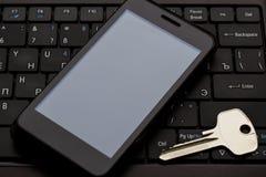 Klucz i telefon komórkowy przy klawiaturą Zdjęcia Royalty Free