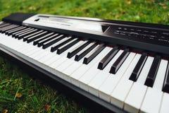 Klucze elektryczny pianino, zielonej trawy tło obraz royalty free