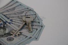 Klucze kłamają na dolarów rachunkach fotografia stock