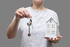 Klucze od domowego pojęcia kobieta trzyma małego dom i wpisuje w jej ręce Zakup nieruchomość Nieruchomości usługa dla kupować twó Zdjęcie Stock