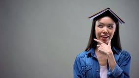 Kluge Frau mit Buch auf dem Kopf, der ?ber Ideen f?r neuen Start, Berechnungen denkt lizenzfreie stockfotografie