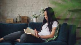 Kluge junge Dame mit dem langen dunklen Haar ist Lesebuch und der Holdingtasse kaffee, der herein auf Couch im Wohnzimmer sitzt stock video footage