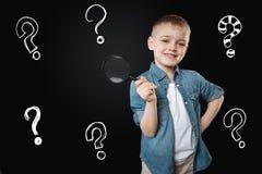 Kluger Junge, der eine Lupe bei der Erforschung der Welt hält Lizenzfreies Stockfoto