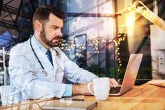 Kluger junger Doktor, der an seinem Laptop arbeitet und ernst schaut stockbilder