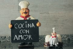 Kluger Koch mit Tafel in der Hand, die K?che mit Liebe sagt lizenzfreie stockfotos