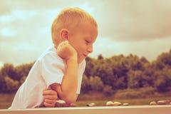 Kluges Kind des kleinen Jungen, das Kontrolleure im Park spielt Lizenzfreies Stockfoto