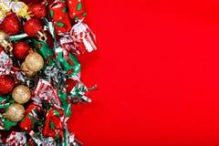 Klumpa ihop sig bakgrund för ferieparti, nytt år, jul eller födelsedaggodis och blänka bollen på röd bakgrund Fotografering för Bildbyråer