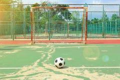 Klumpa ihop sig framme av futsal mål på gatan som är futsal med solsignalljuset Royaltyfria Bilder