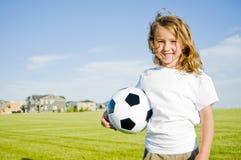 Klumpa ihop sig hållande fotboll för flicka att le Arkivbild