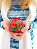 Klumpa ihop sig hållande jul för en flicka i händerna Royaltyfri Fotografi