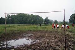 Klumpa ihop sig matchen, spelare som kör i gyttjan, bollgyttja, 07 2011 Polen Royaltyfria Foton