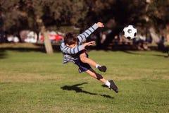 Klumpa ihop sig sparka fotboll för pojke arkivfoto