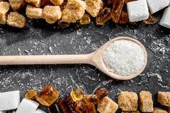 Klumpen des Zuckers mit Löffelbonbon stellten auf dunkles Draufsichtmuster des Tabellenhintergrundes ein Lizenzfreie Stockfotografie