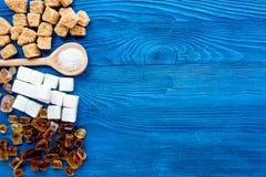 Klumpen und versandender Zucker für Bonbons auf blauem Draufsichtspott des Küchentischhintergrundes oben Lizenzfreies Stockfoto