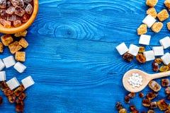 Klumpen und versandender Zucker für Bonbons auf blauem Küchentisch backgro lizenzfreie stockbilder