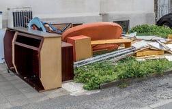 Klumpig avfalls med skåp, en soffa och möblemang på gräsmattan framme av en hyreshus arkivbilder