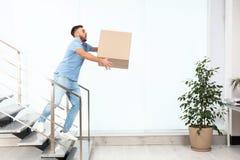 Klumpig för lådaask för ung man bärande bottenvåning inomhus royaltyfri fotografi
