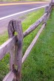 Kluvet stångstaket, gräs och Blacktop Royaltyfri Fotografi