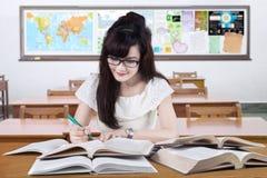 Klyftig elev som studerar i klassrumet Arkivfoto