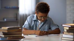 Klyftig manlig elev som gör matematikläxa som löser likställande i anteckningsbok, kunskap royaltyfri foto