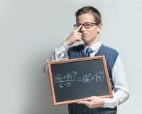 Klyftig skolpojke i exponeringsglas med matematisk likställande Arkivbilder