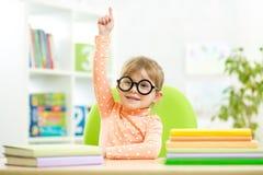 Klyftig ungebarnflicka med böcker inomhus royaltyfri foto
