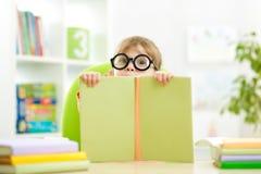 Klyftig ungeliten flicka bakom av den öppna boken inomhus Arkivbild