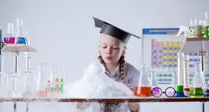 Klyftiga flickablickar på resultatet av det kemiska experimentet Arkivbild