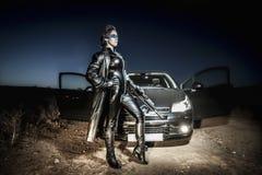 Kämpe iklädd svart latex för farlig kvinna som beväpnas med vapnet. Fotografering för Bildbyråer