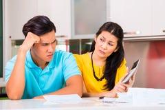 Kämpfende unbezahlte Rechnungen der asiatischen Paare Stockfotos