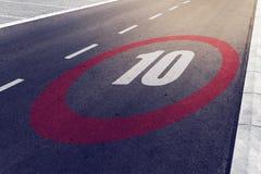 kmph 10 oder MPH-Fahrgeschwindigkeitshöchstgeschwindigkeitszeichen auf Landstraße Lizenzfreies Stockfoto