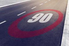 kmph 90 oder MPH-Fahrgeschwindigkeitshöchstgeschwindigkeitszeichen auf Landstraße Lizenzfreies Stockbild