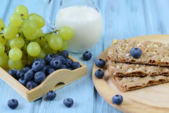 Knäckebrödet med blåbäret, druvor och mjölkar på en träbakgrund Arkivbild