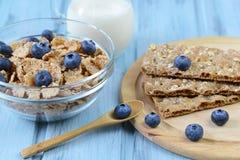 Knäckebrödet och sädesslag med blåbäret och mjölkar på en träbakgrund Royaltyfria Bilder