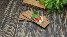 Knäckebrood met zachte kwark en Spaanse peper stock videobeelden