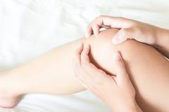 Knäet för innehavet för Closeupkvinnahanden med smärtar på säng, hälsovård royaltyfri fotografi