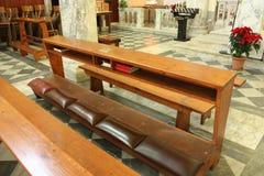 Knäfalla för troget ber i kyrkan arkivbilder