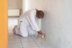 Knäfalla hem- dekoratör som är upptagen med att tejpa golvtegelplattor Royaltyfri Foto