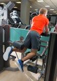 Knäfalla lår- krullningsman för ben på idrottshallen Arkivbilder
