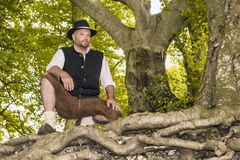Knäfalla man i traditionella bayerska dräkter Fotografering för Bildbyråer