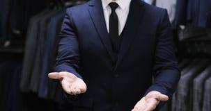 Knäppas ett omslag Stilfull man i en dräktdemonstration av pekskärmhandgester close upp lager videofilmer
