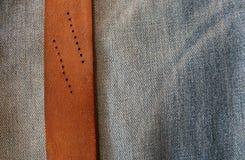 Knäppt fast läderbälte på jeansbakgrund Arkivbild