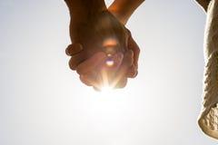 Knäppte fast händer mot en ljus solsignalljus Royaltyfria Foton