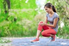 Knäskada - sportar som kör knäskador på kvinna Arkivfoton