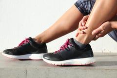 Knöchelschmerz - weiblicher Läufer, der schmerzliche verstauchte gemeinsame Beinnahaufnahme hält Stockfotografie