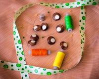 Knöpfe mit gelbgrünem Band und Spulen mit Thread Stockfoto